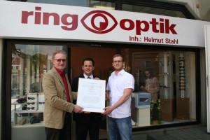 Bürgermeister Frank Keppeler überreicht Helmut Stahl und Optikermeister André Hauschke die Urkunde