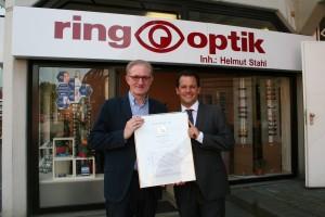 Bürgermeister Frank Keppeler gratuliert Helmut Stahl zu der Auszeichnung, die das ring- optik Fachgeschäft als 1a-Augenoptiker ausweist.